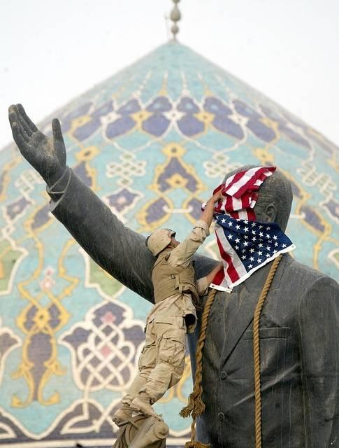 USA med allierte invaderteIrak og styrtetSaddam Husseins regime i 2003. Bildet viser en amerikansk soldat som legger USAs flagg over en statue av Saddam Hussein for å markere seier.Foto: AP Photo/Laurent Rebours/Flickr