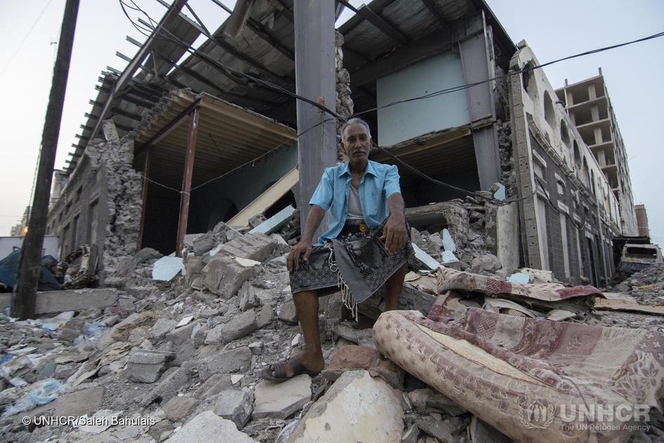 """52 år gamle Shaker Ali sitter foran det som var et marked i Aden. """"Jeg har bodd her i over 15 år, og å se nabolaget mitt slik gjør meg trist. Krigen tvang oss til p flykte"""", sier han. ©UNHCR/Saleh Bahulais"""