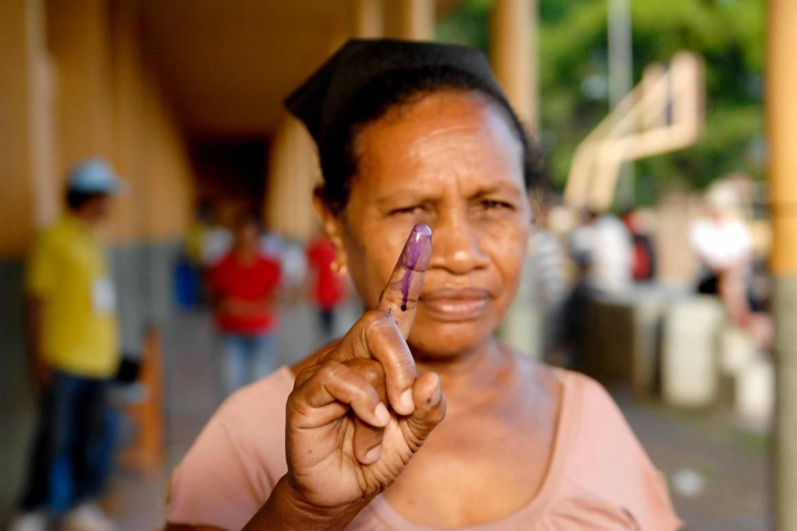 En kvinner viser fram en finger dyppet i blekk. Det beviser at hun har stemt ved valget. Fra Øst-Timor i 2012. Foto: UN Photo/Bernardino Soares