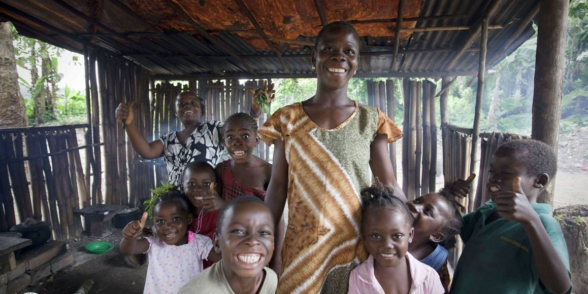 En familie ler mot fotografen. Bildet er tatt i byen Clay Ashland i Liberia i 2011. Foto: UN Photo/Staton Winter