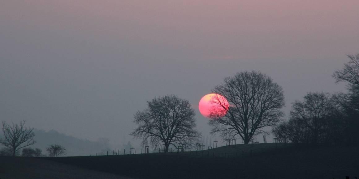 En stor, rød sol er på vei ned i horisonten. Foto: myri_bonie CC BY-NC-ND 2.0