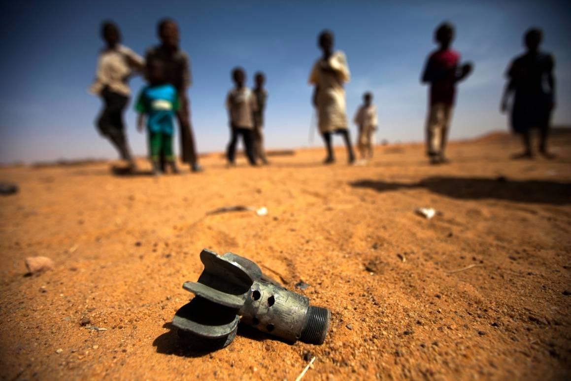 Restene av en bombekasterhar havneti en flyktningeleir iDarfur der barn leker. Foto:UN Photo/AlbertGonzálezFarran