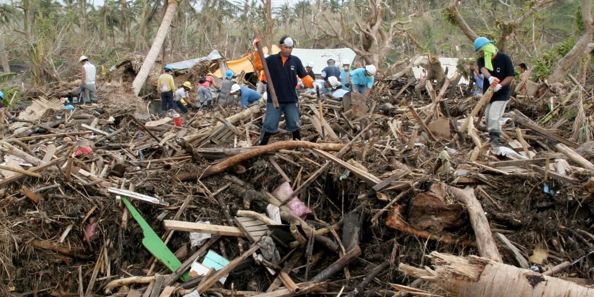 Overlevende og redningsmannskap går gjennom restene av en landsby etter at en storm utløste et jordskred i Bicol, Filippinene i 2007. Foto: Jason Gutierrez/IRIN