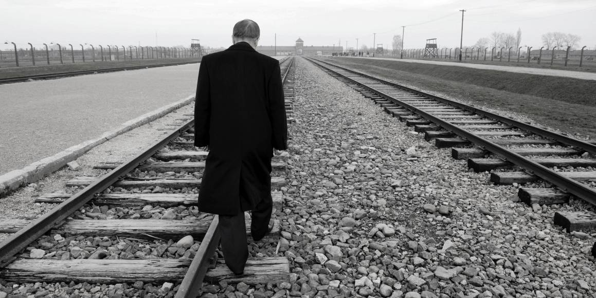 Ban Ki-moon går bortover jernbanelinjene inn til Auschwitz, under et besøk i konsentrasjonsleiren i 2013.
