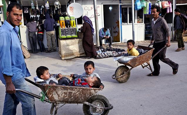 Bildet viser syriske flyktninger som bruker trillebårer som barnevogn. De går i handlegaten i flyktningleiren Zaatri i Jordan, hvor det blant annet selges sko, bleier og elektronisk utstyr. Foto: S. Baldwin/UNHCR