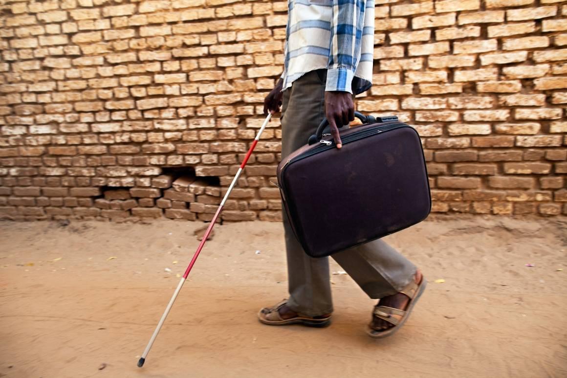 En blind universitetsstudent går med hvit stokk ved Sudanese Association for Disabled Peoples kontor i El Fasher, Darfur. Foto: UN Photo/Albert González Farran