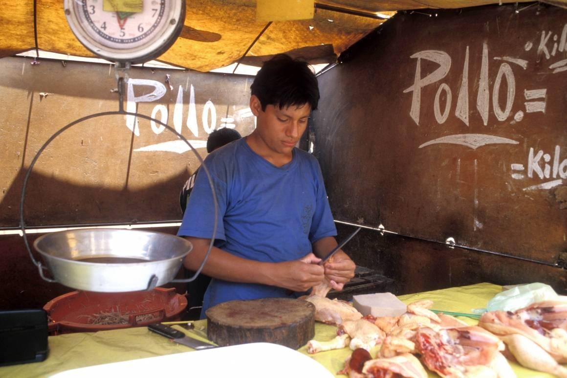 Nedgangstidene merkes over hele Latin-Amerika. Her forbereder en selger mat på et marked i Lima, Peru. Foto: ILO/Lord R.
