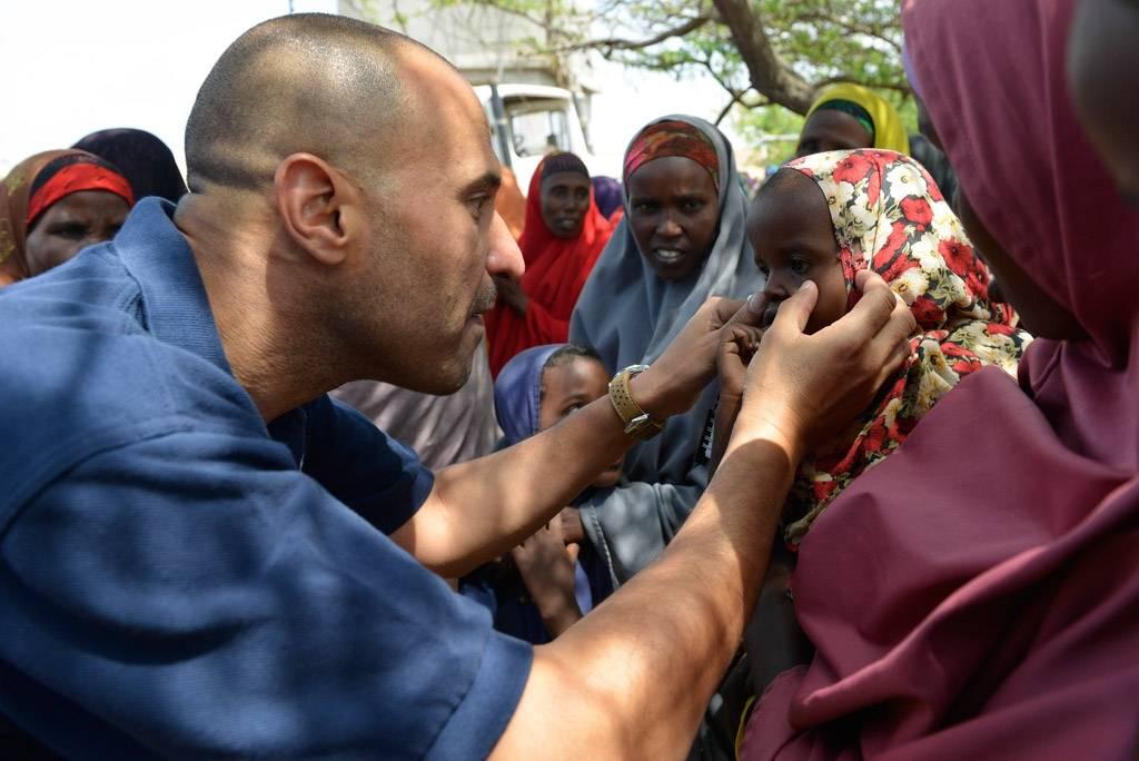 Verdens helseorganisasjon (WHO): Dr. Ahmed El Ganainy undersøker øynene til en liten jente under et humanitært oppdrag i Somalia i 2014. Foto: UN Photo/David Mutua