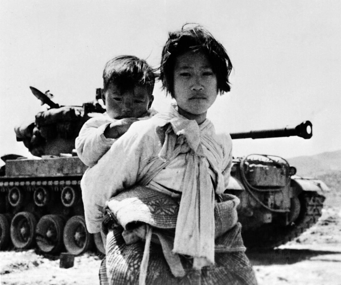En ni år gammel jente bærer på sin lillebror. Bildet av dette foreldreløse søskenparet på flukt ble tatt under Koreakrigen, 9. juni 1951.Foto: UN Photo/United States Navy.