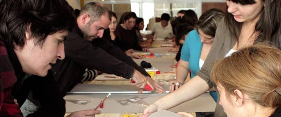 Unge mennesker som klipper og limer rundt et bord. Argentina/International Fund for Cultural Diversity (IFCD)/©UNESCO
