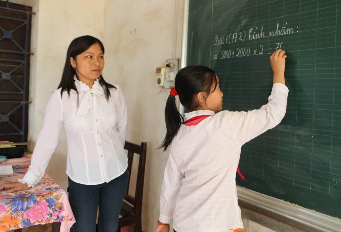 En lærer og eleven hennes løser mattestykker på en skole i Vietnam. Foto: ILO/Truong Van Vi