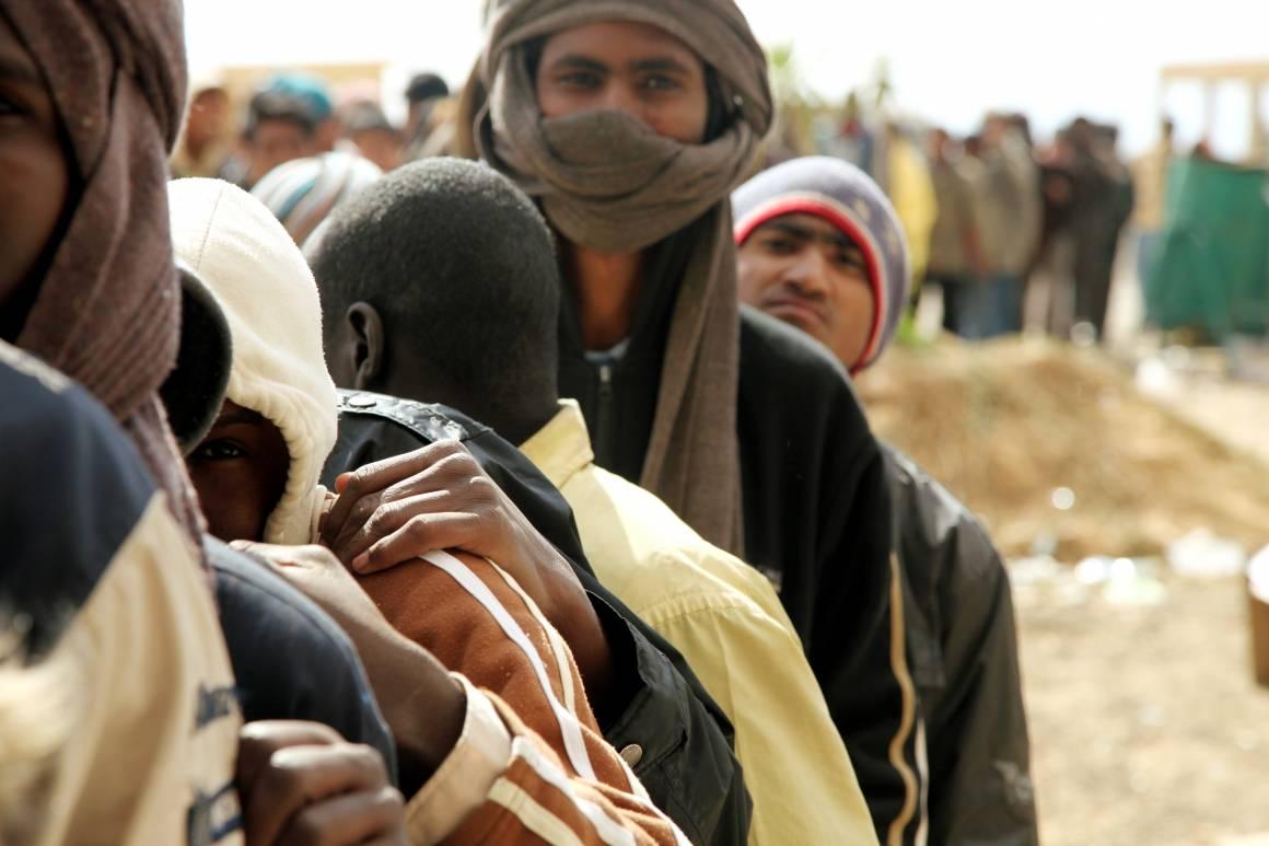Flyktninger står i kø for å få utdelt mat i den egyptiske byen Sallum, på grensen til Libya. De har flyktet fra kamper i Libya, 12. mars 2011. Foto: UN Photo/OCHA/David Ohana
