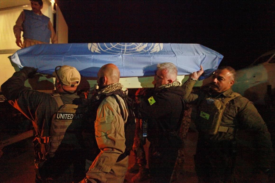 Kisten til en av de syv omkomne FN-ansatte etter angrepet på UNAMA-basen i 2011 blir båret til flyet som skal frakte den hjem. Foto: UN Photo/Eric Kanalstein