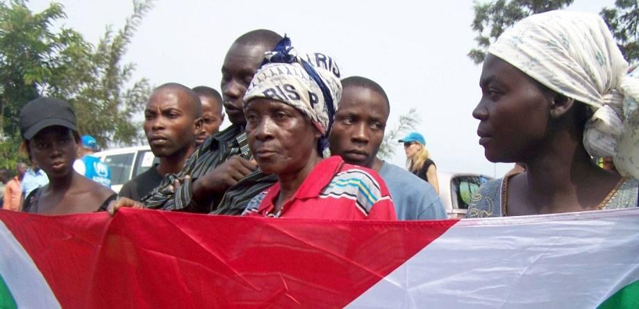 En gruppe flyktninger som returnerer til Burundi fra DR Kongo holder landets flagg mens de hører på en velkomsttale på grensen. IRIN/Judith Batusama