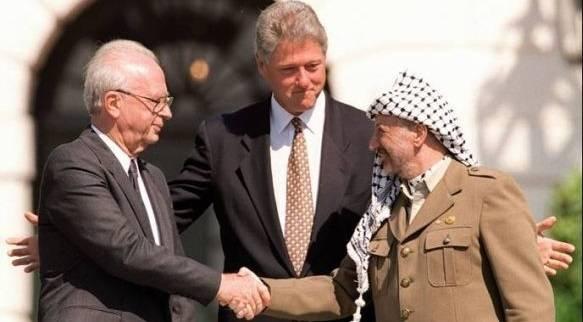 Israels statsminister, Yitzhak Rabin (t.v.), med USAs president Bill Clinton og palestinernes leder, Yassir Arafat, under signeringen av Oslo-avtalen i 1993.