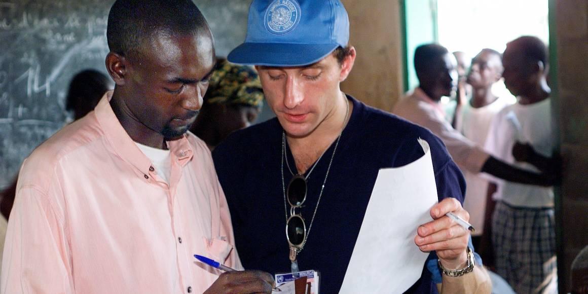 En valgobservatør fra FN hjelper en mann før han skal stemme under valget i 1998. UN Photo/Evan Schneider