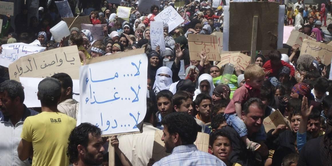 """Folk samler seg i byen Nawa, nær Deraa i april 2011, i en av de første demonstrasjonene mot regimet. På skiltet står det """"Ikke noe vann, ikke noe medisin, ikke noe mat."""" Foto: REUTERS/Handout"""