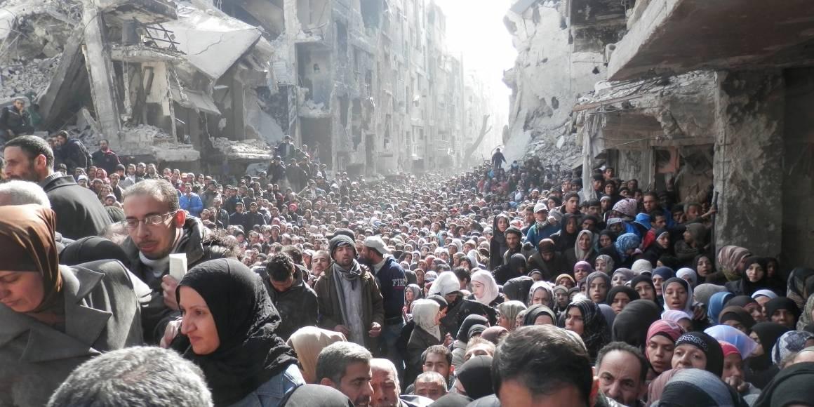 Palestinske flyktninger i Syria står i kø for å få mat fra FN i 2014. Foto: Zuma Press/UNRWA.