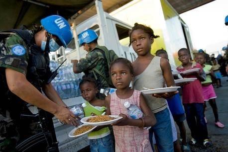 FNs ferdstyrker deler ut vann og mat til innbyggerne fra Cite Solei. Bilde: UN Photo/Marco Dormino