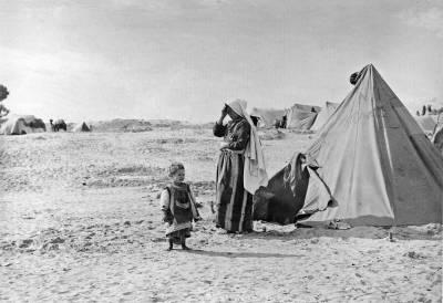 En palestinsk kvinne står sammen med barnet sitt utenfor teltet sitt i flyktningleiren Khan Younis i 1949. Foto: UN Photo
